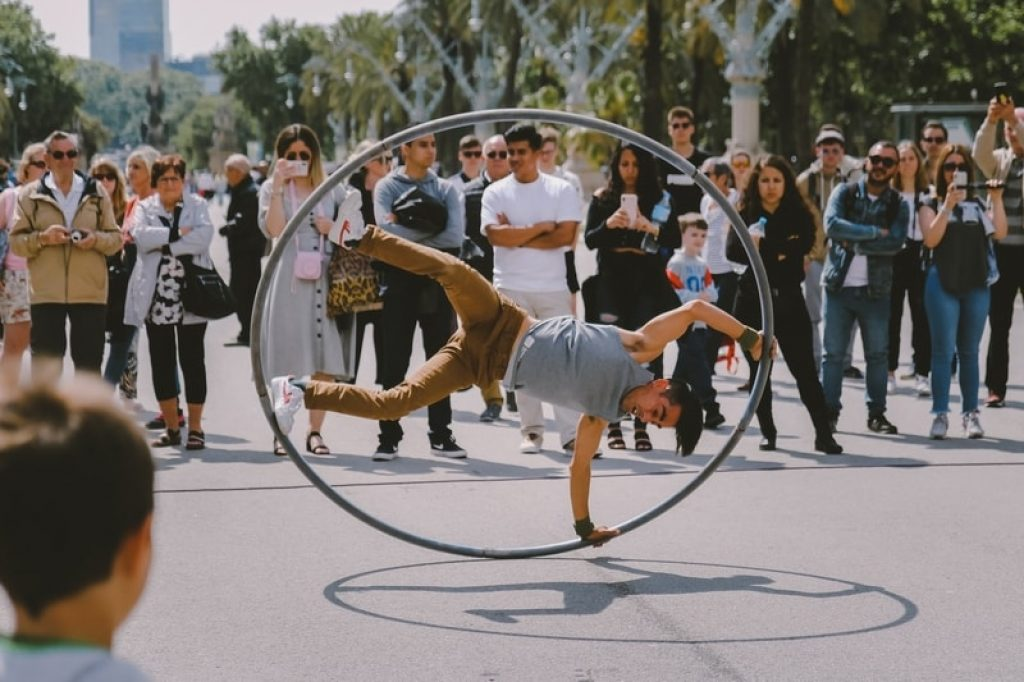 street-artist-performing-stunt-with-big-hula-hoop-with-a-crowd-watching