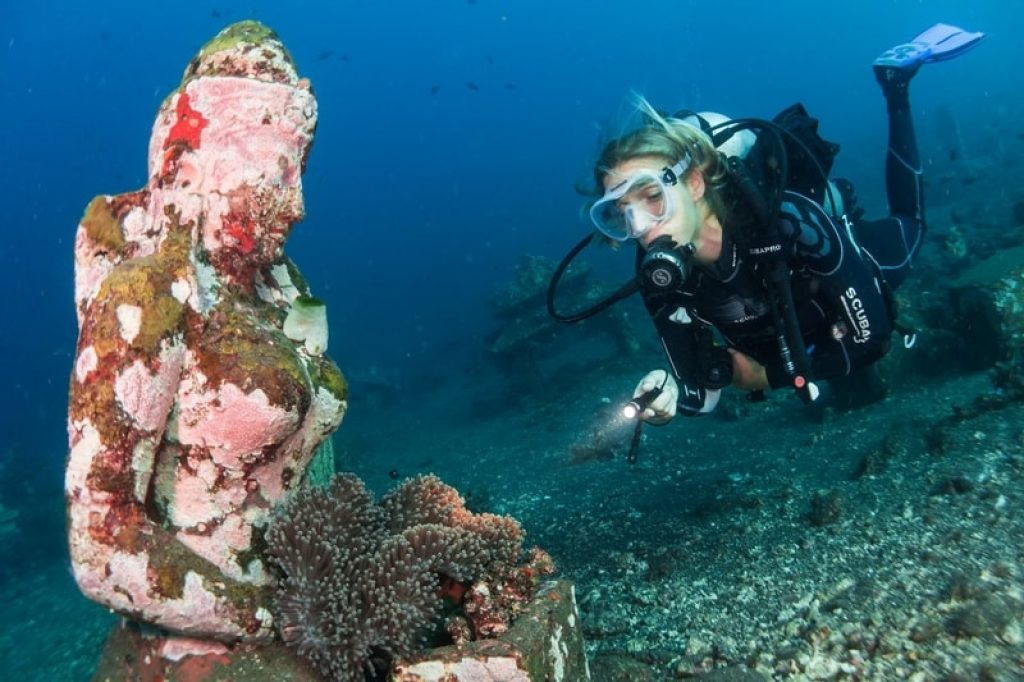 Girl scuba diving with underwater statues